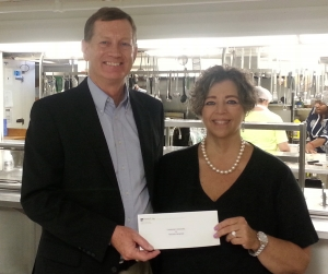 Mark O'Donnell, Executive Director of the Patrick P. Lee Foundation, presents a check to Robyn L. Krueger, Executive Director of Community Missions, to purchase food for the Community Soup Kitchen.